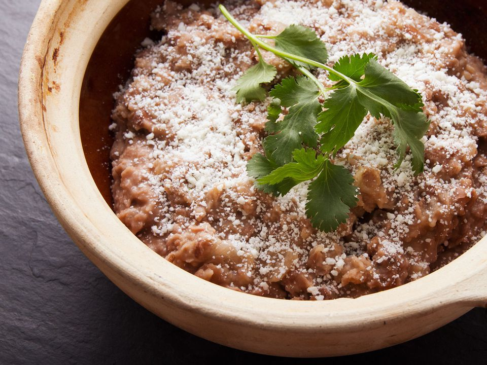 Bowl of refried beans topped with cotija cheese and cilantro