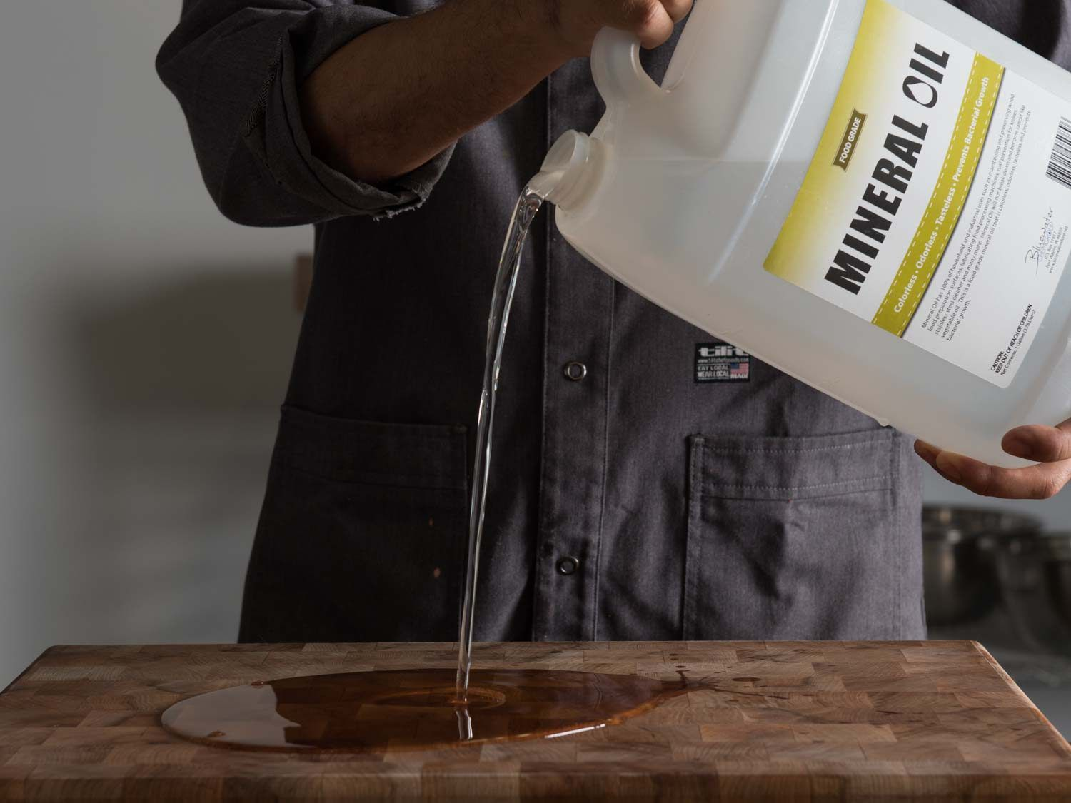 pouring mineral oil onto wood cutting board